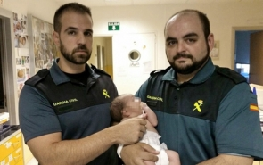 The Guardia Civil officers with the baby they rescued from the bin (Photo: EPA)