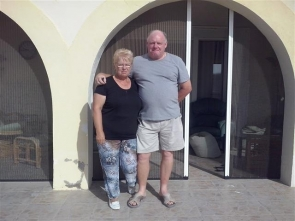 Mr and Mrs Armer outside the doors where they suspect the burglars entered their house