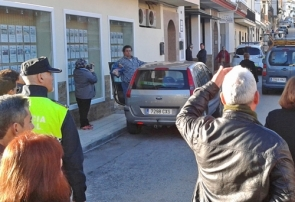 Onlookers watch as the man prepares to get into his car with the petrol-filled bottle
