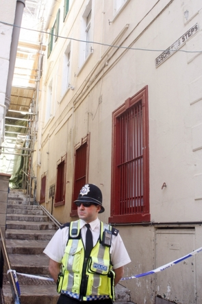 A Gibraltar policeman stands next to a house on Boschetti's Stepswhere a Britsh family has been found dead