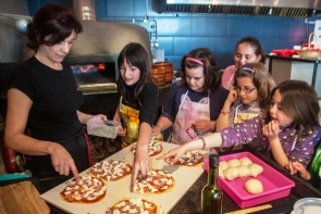 Chef Carina shows Lubrin children how to make pizzas