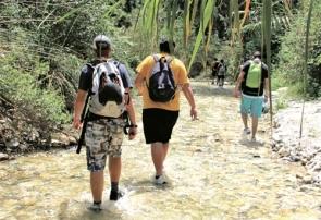 Hikers walking up the riverbed at Río Chíllar