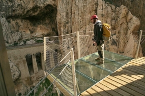 A worker standing on a glass platform on the Caminito